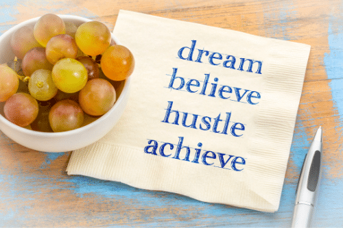 dream believe hustle achieve written on napkin
