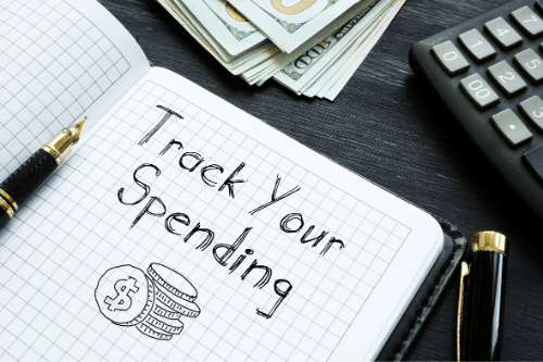 track your spending written in notebook